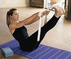 femme qui utilise des accessoires de yoga comme une brique et une ceinture