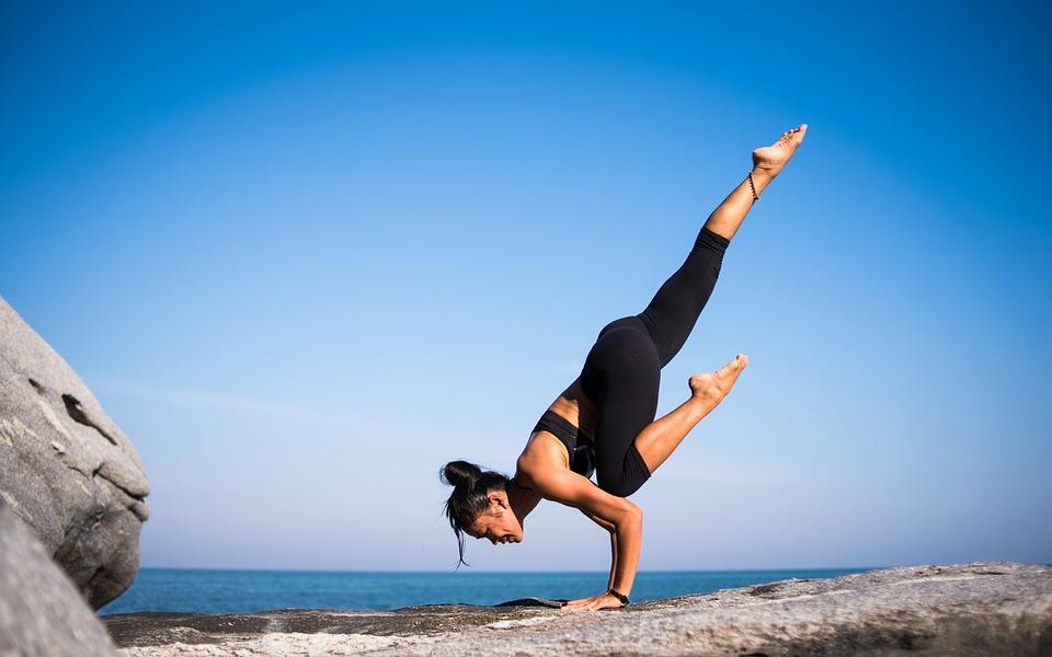 femme qui fait du yoga à la mer pour se détendre. Elle n'utilise pas de tapis. Et il y a un ciel bleu