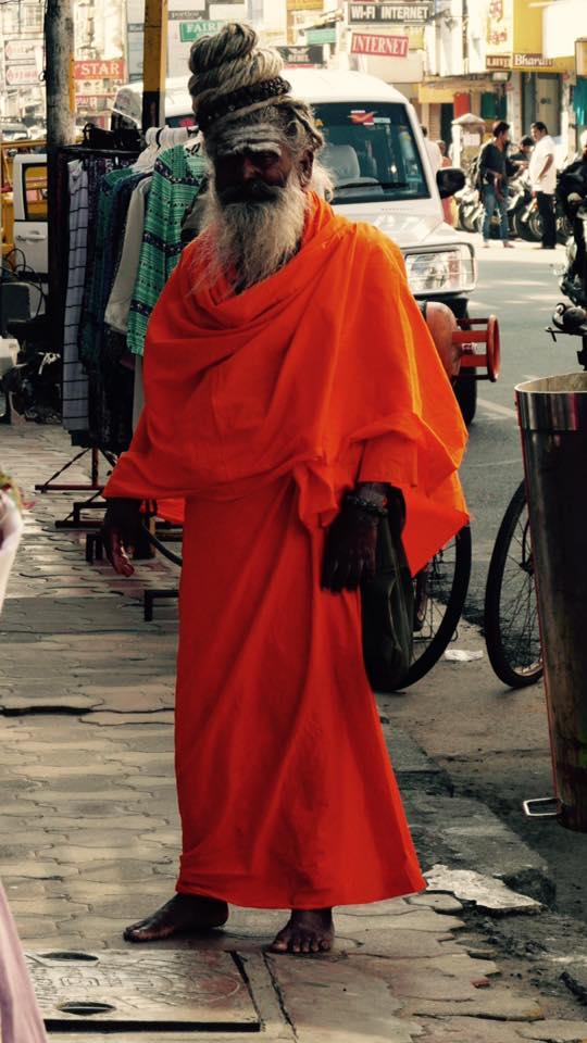 sadhu dans la ville avec des vélos autour. Il marche pieds-nus et porte un habit orange