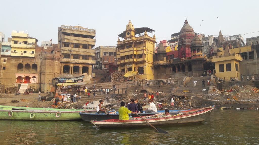 ghat de varanasi où on incinère les morts 24h/24. On y voit des barques. Il y a une maison de couleur jaune