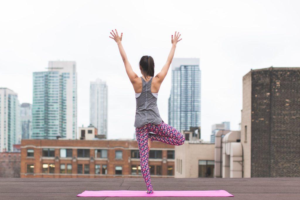 yoga à la pause en entreprise. On voit une femme qui fait une pose dans une ville.